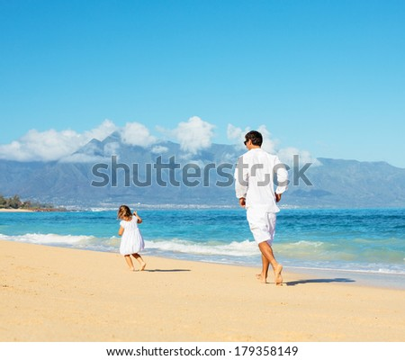 Healthy father and daughter walking together at the beach  - stock photo