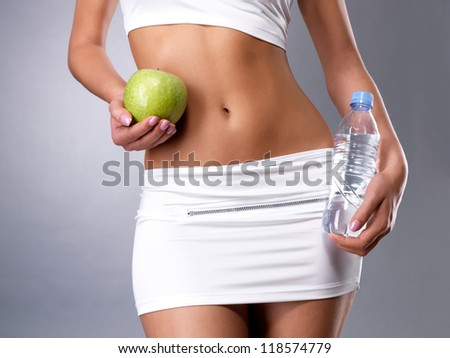 Healthy female body with apple and bottle of water. Healthy fitness and eating lifestyle concept. - stock photo