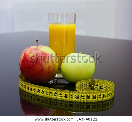 Healthy fiber rich diet food - fruits and glass of orange  juice on black table with measuring tape, weight loss nutrition. - stock photo