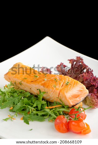 Healthy fish cuisine : baked pink salmon steaks garnished with tomatoes and rocula on white dish - stock photo