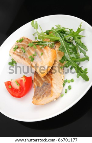 healthy fish cuisine  : baked pink salmon steaks garnished with tomatoes and rocula on white dish isolated over black background