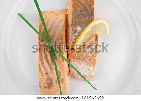 healthy fish cuisine : baked pink salmon steaks with green onion and lemon on white dish isolated over white background - stock photo