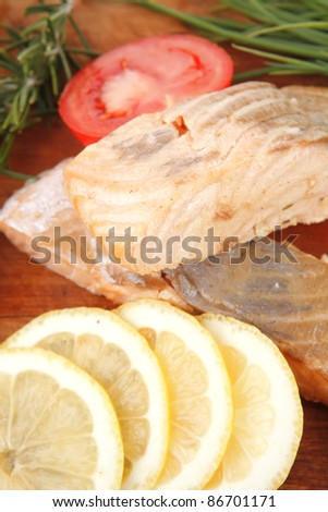 healthy fish cuisine : baked pink salmon steaks with green onion, cherry tomatoes, rosemary twigs and lemon on wooden board isolated on white background