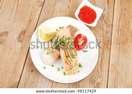 healthy fish cuisine  : grilled pink salmon steaks on white dish with red caviar over wooden table