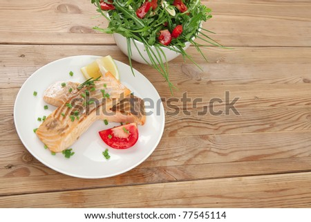 healthy fish cuisine  : grilled pink salmon steaks with vegetable salad on white dish over wooden table - stock photo