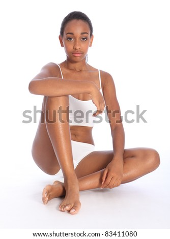 Healthy fit body of beautiful young black woman sitting on the floor, wearing white sports underwear and bare foot. Taken on white background. - stock photo