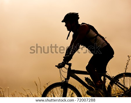 healthy fit man in silhouette rides his mountainbike outdoors at dusk, carefree bicycle fitness - stock photo