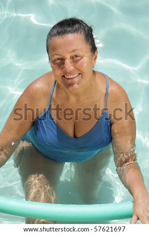 Healthy, fit older woman exercising in the pool - stock photo