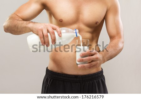 Healthy fit shirtless Caucasian muscular young man pouring milk from bottle to glass. Closeup studio shot. Healthy lifestyle and healthy eating concept. - stock photo