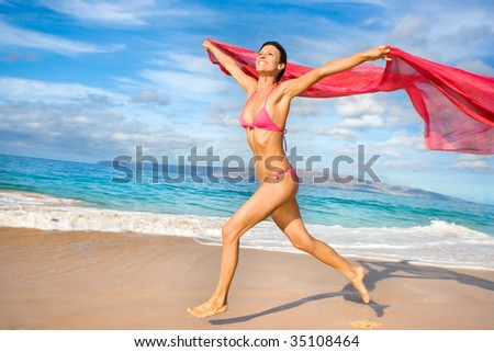healthy fit woman with pink sarong running on tropical beach smiling in pink bikini - stock photo
