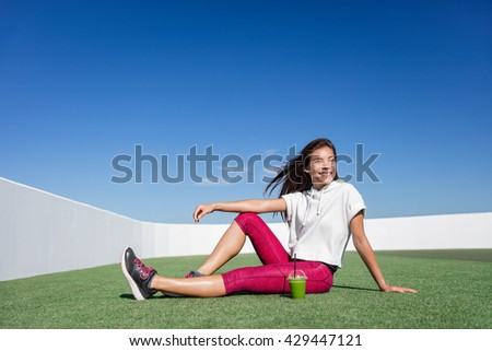 Healthy fitness Asian woman drinking green smoothie. Happy relaxing sporty athlete during strength training workout break in outdoor summer enjoying vegetable juice morning breakfast in activewear. - stock photo