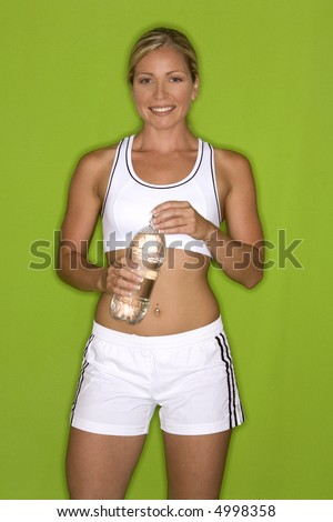 healthy fitness model posing on green isolated background - stock photo