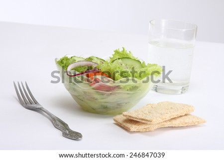 healthy food: a bowl of fresh salad, crisps, a glass of water, a fork - stock photo