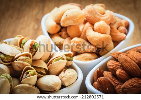 Healthy food and cuisine. Varieties of nuts: cashew, pistachio, almond - stock photo