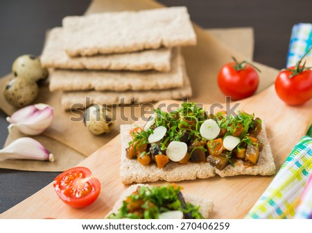 Healthy food. Appetizer. Crispbread with steamed vegetables (eggplant, carrot, onion) with garlic, parsley - stock photo