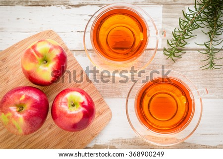 Healthy food arrangement with red apples on a wooden board, two glass cups of herbal or black tea and rosemary leaves on a rustic wooden table. View from above/top.