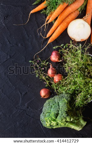 Healthy food background with raw vegetables and herbs. Carrots, onions, broccoli and thyme over black textured surface. Flat lay. Copy space for text. - stock photo