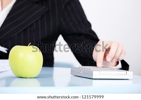Healthy food concept. Apple on office desk, businesswoman working in background.