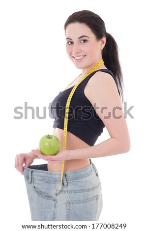 healthy food concept - beautiful slim woman in big jeans with apple and measuring tape isolated on white background - stock photo