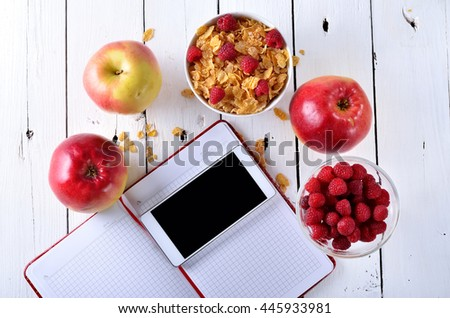 Healthy food concept: cereal berries and apple on a wooden table. Notebook and phone for recording diet. - stock photo