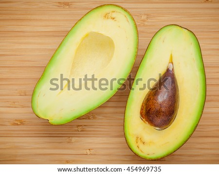 Healthy food concept.Closeup ripe avocado on wooden background. Halved organic avocado with core on wooden background.  Top view with copy space. - stock photo