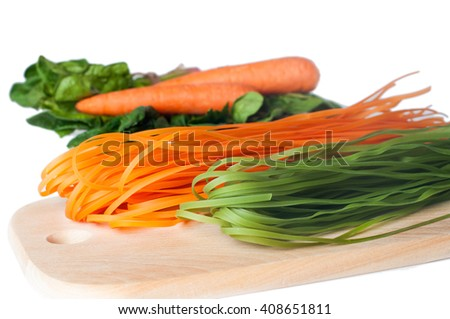 Healthy food concept: colorful raw italian pasta with its natural vegetable dyes (spinach, carrot) on wooden desk, isolated over white background. Shot in shallow depth of field - stock photo