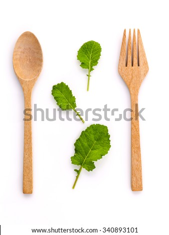 Healthy food concept fresh organic green leaves with wooden fork and spoon isolated on white background cutout .