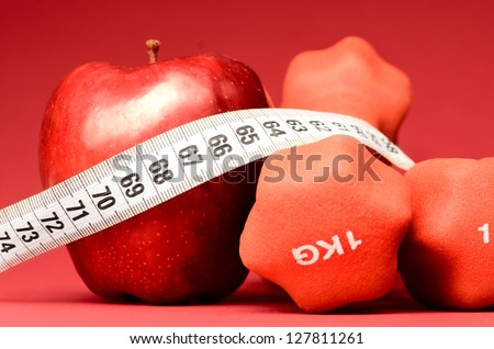 healthy food. Delicious apple with measuring tape and dumbbells on red - stock photo