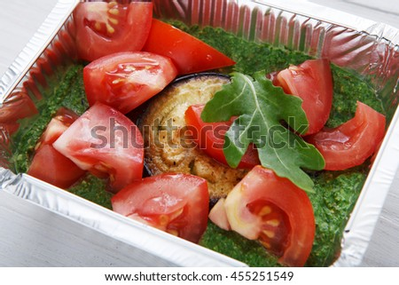 Healthy food delivery and diet concept. Take away of fitness meal. Weight loss nutrition in foil boxes. Roasted eggplant with guacamole and fresh tomatoes, closeup at white wood - stock photo