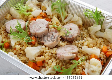 Healthy food delivery and diet concept. Take away of fitness meal. Weight loss nutrition in foil boxes. Bulgur pilaf with fish rolls and boiled cauliflowers closeup at white wood - stock photo