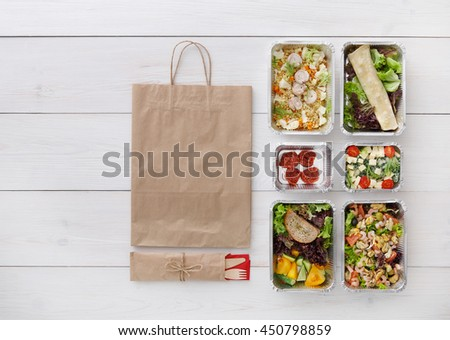 Healthy food delivery. Take away for diet. Fitness nutrition, vegetables, meat and fruits in foil boxes, cutlery and brown paper package. Top view, flat lay at white wood with copy space - stock photo