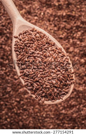 Healthy food diet. Closeup brown flax seeds linseed on wooden spoon - stock photo