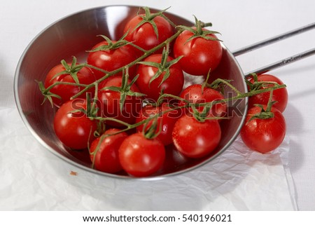 Healthy food & drink Italian healthy lifestyle. Mediterranean fresh vegetables spices &  herbs. Red cherry tomatoes in a skillet on the kitchen table. Top view White background Closeup