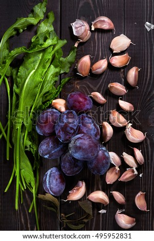 Healthy food & drink & natural diet food & home cooking. Natural organic food: garden fruits herbs vegetables & spices. Sorrel, plums & garlic. Seasonal vegetables diet food Wooden background Top view