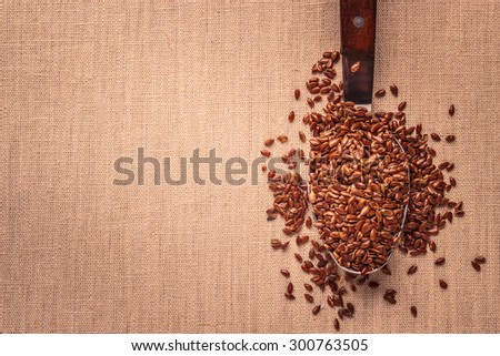 Healthy food. Flax seeds linseed on kitchen spoon burlap sack background - stock photo