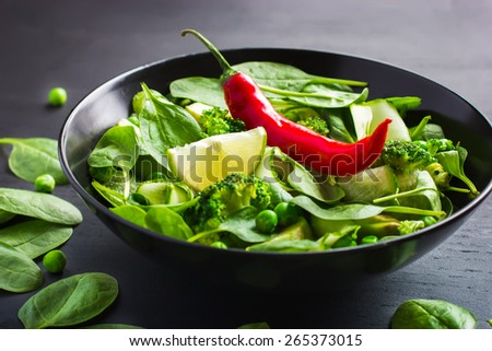 Healthy food. Fresh green salad on black background, selective focus - stock photo