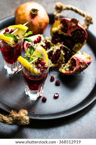 Healthy food,  fresh pomegranate cocktail with lemon on rustic background. Selective focus