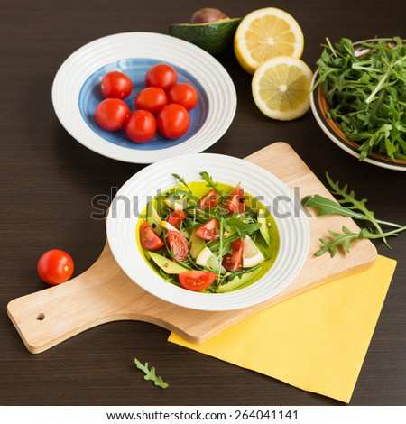 Healthy food. Fresh salad of arugula with cherry tomatoes and avocado