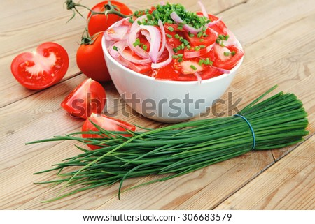healthy food : fresh tomato salad in white bowl with bunch of chives and raw tomatoes on twig , onion,  over wooden table - stock photo