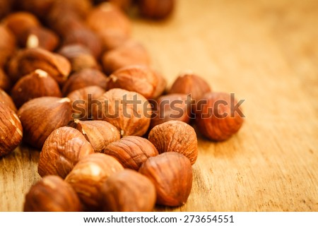 Healthy food full of fatty acids, organic nutrition. Hazelnuts kernel on rustic old wooden table - stock photo