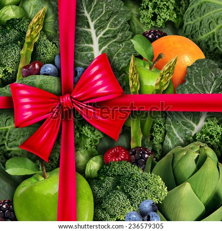 Healthy food gift concept as a group of fresh fruit and vegetables with a red silk bow  packaging ribbon as a diet and fitness lifestyle metaphor and symbol for nutritious holiday giving. - stock photo