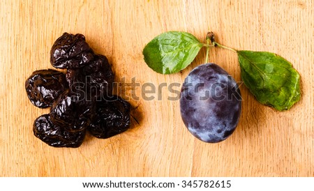 Healthy food, good cuisine. Closeup dried plums and fresh prune fruit on wooden rustic table
