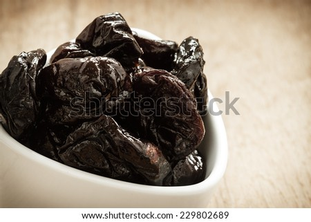 Healthy food, good cuisine. Closeup dried plums prunes fruits in white bowl on wooden rustic table background - stock photo