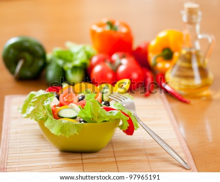 healthy food Greek salad, vegetables and bottle with sunflower oil on wooden table - stock photo