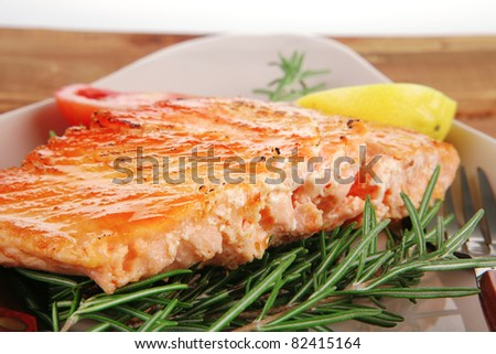 healthy food: hot baked salmon piece served over glass plate on wood - stock photo