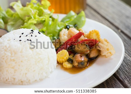 Healthy food in white plate. Rice topped with stir-fried sea food and basil.