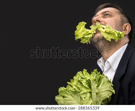 Healthy food. Man holding and eating lettuce on dark background with copy-space - stock photo