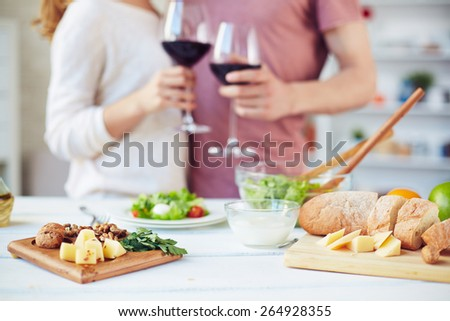 Healthy food on table on background of toasting couple