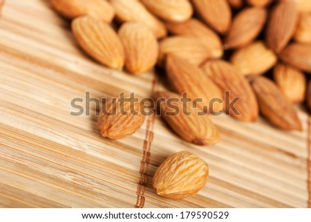 Healthy food organic nutrition.Pile of raw almonds on bamboo background - stock photo