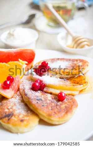 Healthy food, pakcakes with fresh fruits, honey and sour cream, green tea
